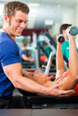 Woman and Personal Trainer in gym, with dumbbells Royalty Free Stock Image