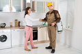 Woman and pest control worker shaking hands happy young to each other in kitchen room Royalty Free Stock Photo