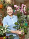 Woman with phalaenopsis orchid at flower shop happy mature Stock Photo