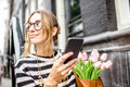 Woman with phone and flowers near the building Royalty Free Stock Photo
