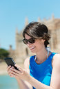 Woman with phone happy in glasses texting cellular outdoors Royalty Free Stock Photos
