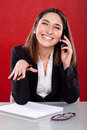 Woman on the phone smiling young sitting at a desk Royalty Free Stock Images