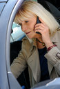 Woman phoning at the wheel a senior of her car Royalty Free Stock Images