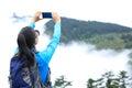 Woman photographer taking photo at emei mountain peak Royalty Free Stock Photo
