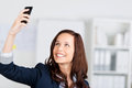 Woman photographing herself with her mobile phone holding it up in the air and smiling Stock Photos