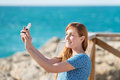 Woman photographing herself with a mobile pretty young phone at the seaside Royalty Free Stock Images