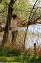 Woman photographing nature springtime standing in bushes on lake and Royalty Free Stock Image