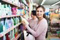 Woman picking bottles with shampoo and conditioner from shelf in Royalty Free Stock Photo
