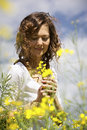 Woman picking flowers in rapeseed field.