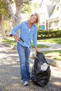 Woman Picking Up Litter In Suburban Street Royalty Free Stock Photography