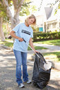 Woman Picking Up Litter In Suburban Street Royalty Free Stock Image