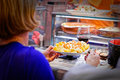 A woman picks up her first dish ready in a market stall at la boqueria barcelona Stock Photo