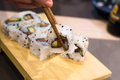 Woman picks up uramaki sushi roll with fresh salmon avocado and philadelphia cheese covered with sesame seeds a young her Royalty Free Stock Photo