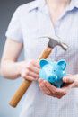Woman with piggy bank and hammer a young holding a a in her hands Stock Photography