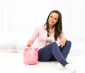 Woman with piggybank cheerful young sitting on a carpet Royalty Free Stock Images