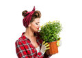 Woman with pin-up hairstyle smelling yellow daisies in flower po Royalty Free Stock Photo