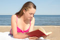 Woman in pink bikini reading book on the beach young Stock Photography