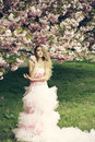 Woman in pink dress near bloom beautiful young glamour with long curly hair spring flowers Stock Images