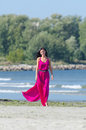Woman in pink dress walking on the beach Stock Images