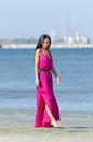 Woman in pink dress walking on the beach Royalty Free Stock Image