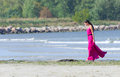 Woman in pink dress walking on the beach place for text Stock Image