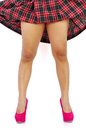 Woman pink high heels and plaid skirt young reveals her legs by lifting up her Stock Photo