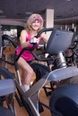 Woman in pink sportswear doing exercise beautiful blonde womanr on bike gym Stock Photography