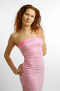 Woman in the pink strapless dress young is wearing a cocktail Stock Photography