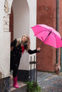 Woman with pink umbrella looking up in front of a house Royalty Free Stock Image