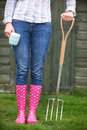 Woman In Pink Wellingtons Holding Garden Fork And Cup Royalty Free Stock Photo