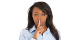 Woman placing finger to lips. Asking to keep secret