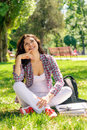 A woman in a plaid shirt sitting on the green grass Stock Photography