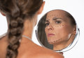 Woman with plastic surgery marks on face looking in mirror isolated white Royalty Free Stock Images