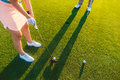 Woman player ready to hit the ball into the hole at the end of a Royalty Free Stock Photo