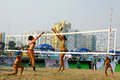 Woman player spiking in beach volleyball game Stock Photos