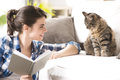 Woman playing with cat smiling her and holding a book in the living room Royalty Free Stock Photos