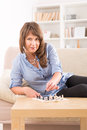 Woman playing chess at home beautiful on mini chessboard Stock Photography