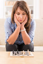 Woman playing chess at home beautiful on mini chessboard Stock Photos