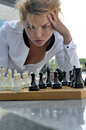 Woman playing chess outdoors. Royalty Free Stock Photo