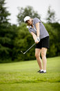 Woman is playing golf on course  summer Royalty Free Stock Photo
