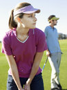 Woman playing golf with male friend young women on golfcourse Royalty Free Stock Image
