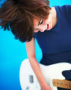 Woman playing a guitar isolated on blue background Stock Photography