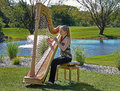 Woman playing a harp on a golf course Royalty Free Stock Photography