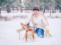 Woman playing with her pet in winter park happy smiling Royalty Free Stock Photos