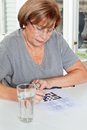 Woman playing leisure games senior with glass of water in foreground Stock Photos
