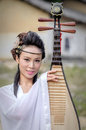 Woman playing the pipa a dressed in ancient costume holding a lute played outdoors minato is a plucked string instrument with four Royalty Free Stock Photography