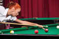 Woman playing pool side view of confident young aiming the billiard ball with cue Royalty Free Stock Photography