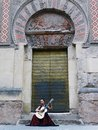 A woman playing a Spanish Flamenco Guitar in front of Mosque Cathedral of Cordoba Royalty Free Stock Photo
