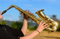 Woman playing a tenor saxophone outdoors side close up view of young in the countryside raising the instrument in the air Royalty Free Stock Image