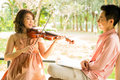 Woman playing violin with her boyfriend young women in garden Royalty Free Stock Photography